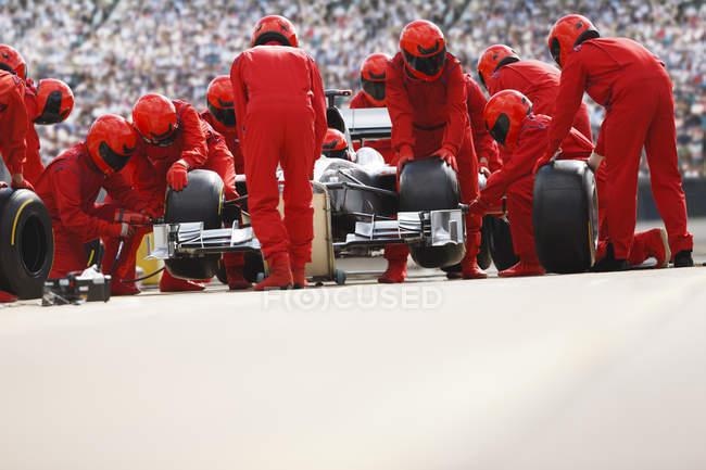 Команда гоночных автомобилей работает на пит-стопе — стоковое фото