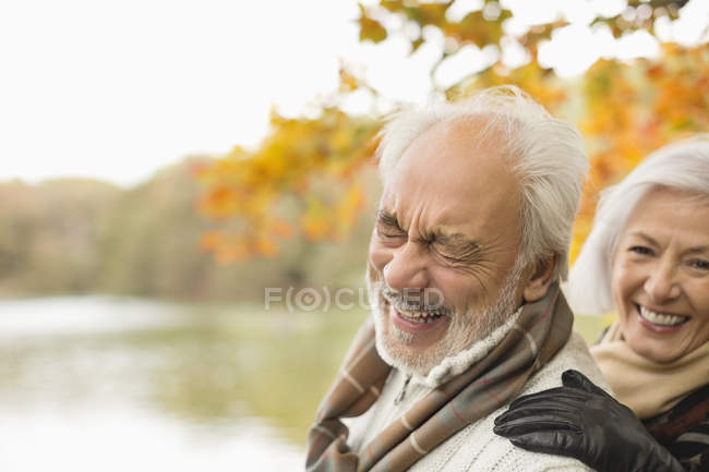 Older couple laughing together in park — Stock Photo