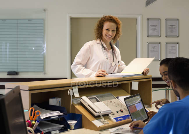 Personal del hospital hablando en recepción - foto de stock