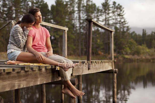 Serene couple sitting at edge of dock over lake — Stock Photo