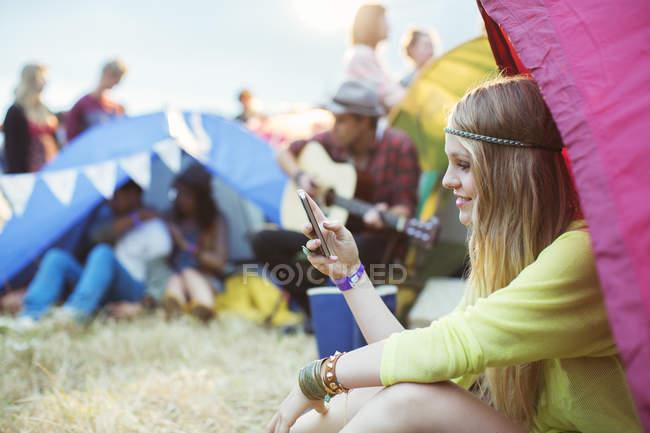 Сообщения с мобильного телефона в палатке на музыкальном фестивале — стоковое фото