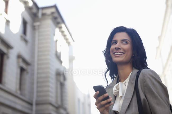 Joyeuse messagerie texte femme d'affaires avec téléphone portable — Photo de stock