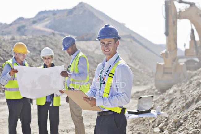 Des hommes d'affaires lisant des plans dans une carrière — Photo de stock