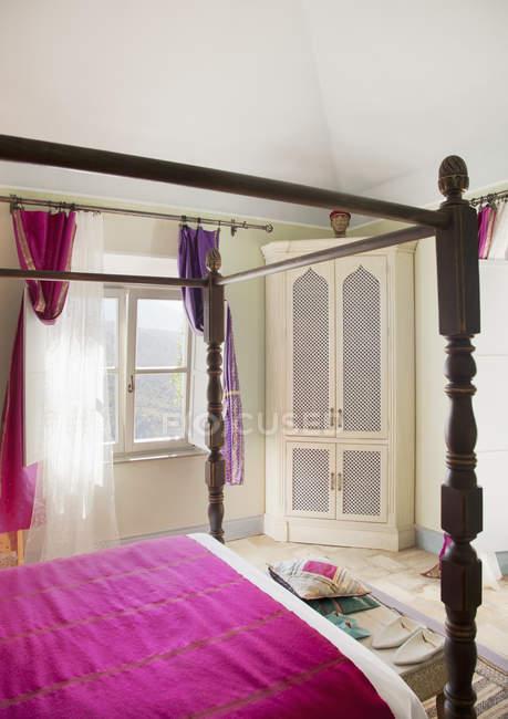 Cama con dosel morado ropa de cama en dormitorio - foto de stock