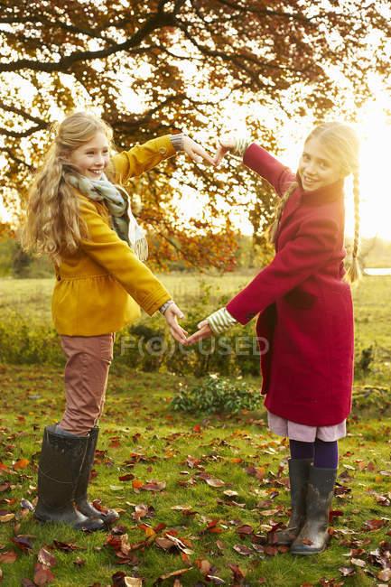 Chicas haciendo forma de corazón con brazos al aire libre - foto de stock