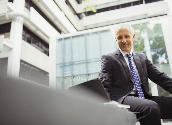 Uomo d'affari che utilizza il computer portatile in edificio per uffici — Foto stock