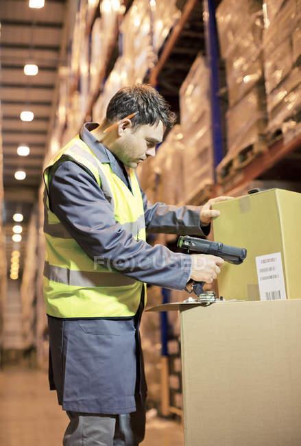 Caja de escaneo del trabajador en almacén - foto de stock