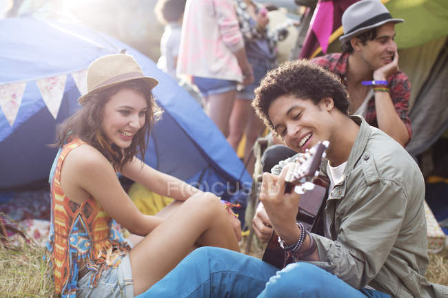 Man playing guitar outside tents at music festival — Stock Photo