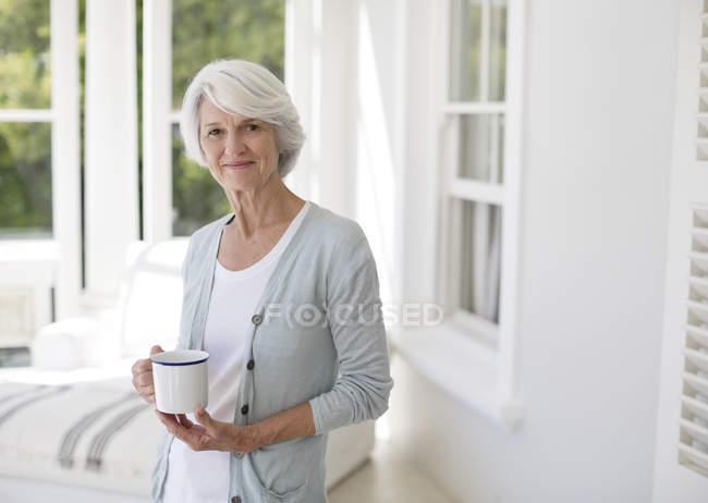 Mujer Senior con taza de café en sala sol - foto de stock