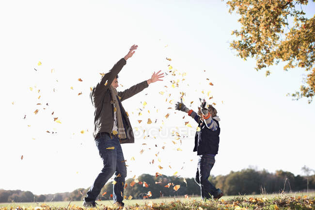 Father and son playing in autumn leaves — Stock Photo
