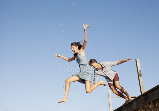 Happy exuberant couple jumping off dock — Stock Photo
