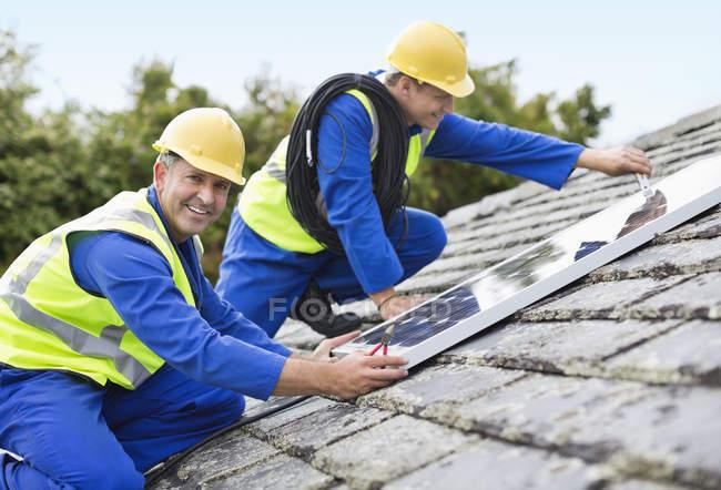 Рабочие устанавливают солнечные батареи на крыше — стоковое фото