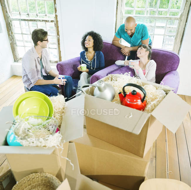 Young happy friends relaxing in new home — Stock Photo