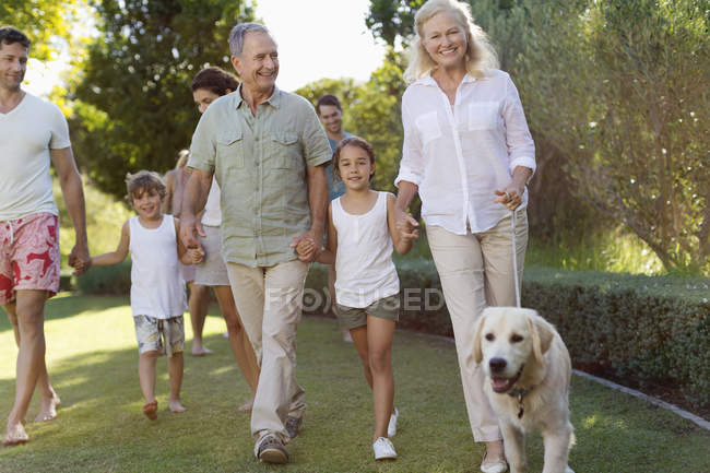 Family walking together in park with dog — Stock Photo