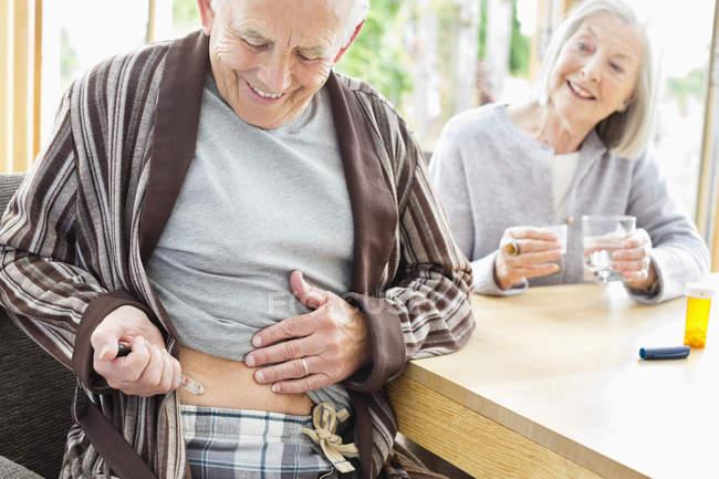 Пожилой человек делает себе укол — стоковое фото