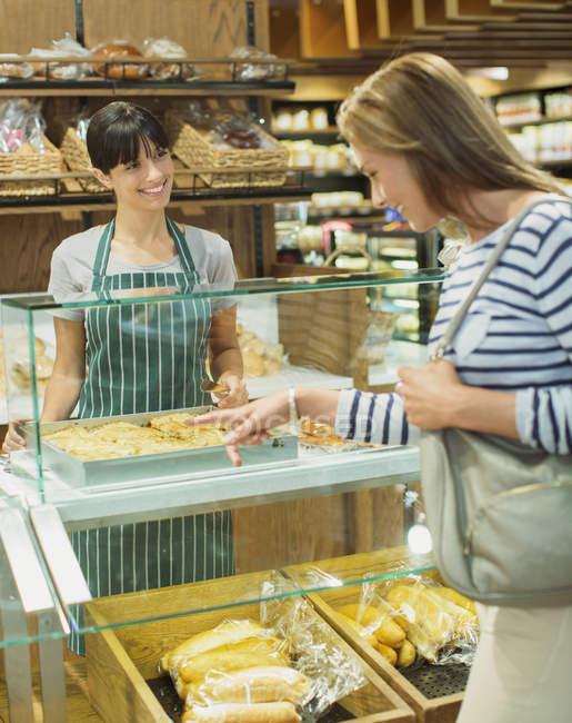 Mulher, fazer compras no balcão de frios em supermercado — Fotografia de Stock