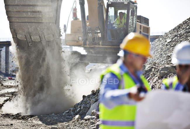 Bagger arbeiten im Steinbruch und Arbeitnehmer im Vordergrund — Stockfoto