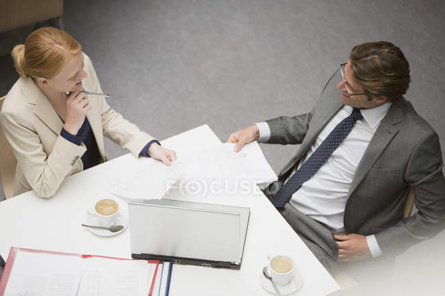 Businessman and businesswoman reviewing paperwork at cafe — Stock Photo