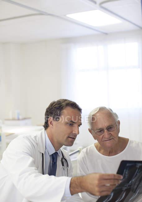 Врач показывает рентген пожилым пациентам в больничной палате — стоковое фото