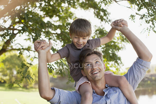 Улыбающийся отец носит сына на плечах под деревом — стоковое фото