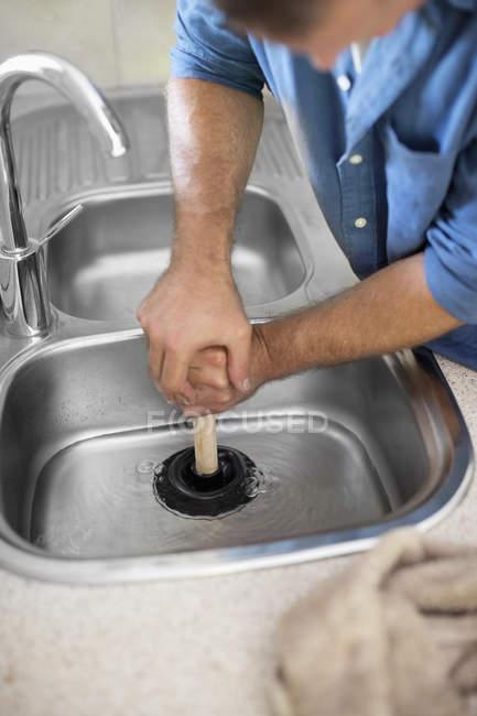 Skillful caucasian plumber unclogging kitchen sink — Stock Photo