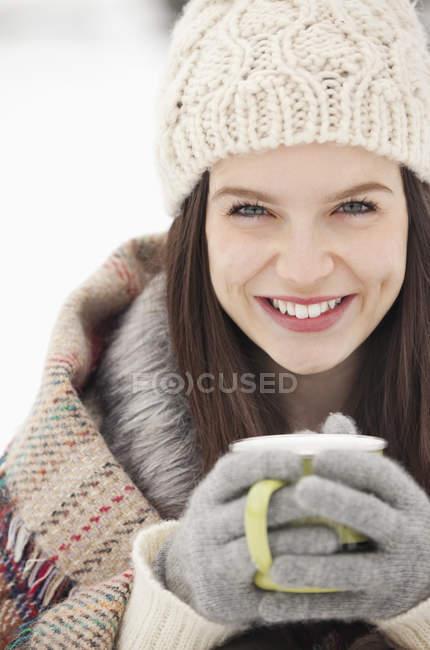 Ritratto ravvicinato di donna in maglia cappello e guanti bere caffè — Foto stock