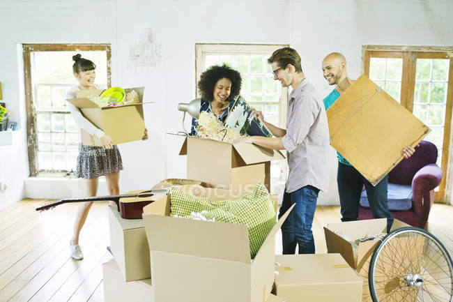 Amigos desembalar cajas en casa - foto de stock