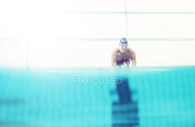Swimmer poised on starting blocks — Stock Photo