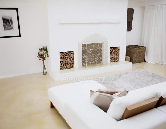 Диваном и камином в современной гостиной — стоковое фото