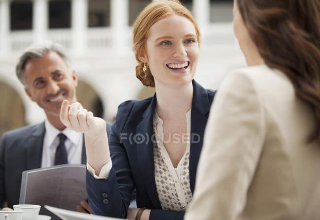 Улыбающиеся деловые люди встречаются в кафе на тротуаре — стоковое фото