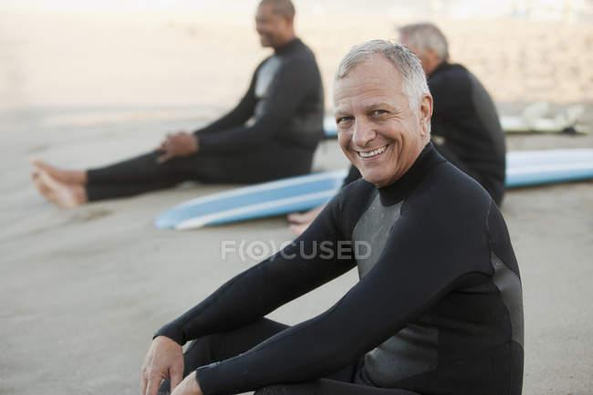 Старшие серферы сидят на досках на пляже — стоковое фото
