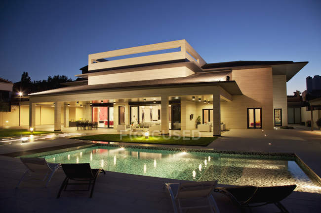 Luxury house and swimming pool illuminated at night — Stock Photo