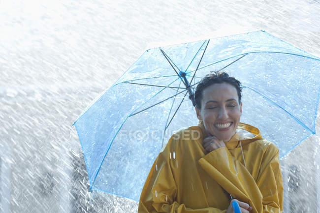 Femme heureuse sous le parapluie sous la pluie — Photo de stock