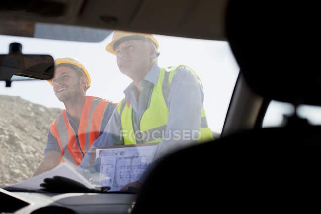 Homme d'affaires et travailleur lisant les plans sur place — Photo de stock