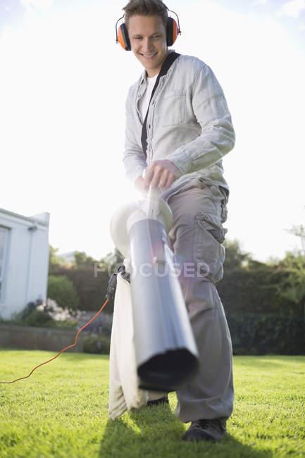 Hábil hombre caucásico soplar las hojas en el patio trasero - foto de stock