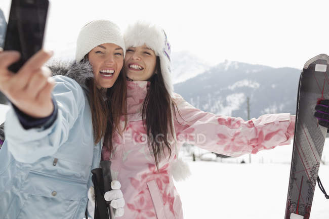 Enthusiastic women with skis taking self-portrait with camera phone in field — Stock Photo