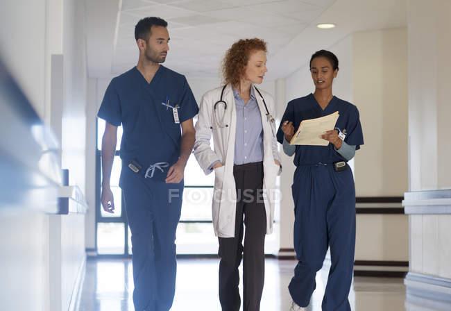 Modernes Krankenhauspersonal spricht auf Flur — Stockfoto