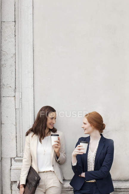 Smiling businesswomen drinking coffee and talking against building wall — Stock Photo