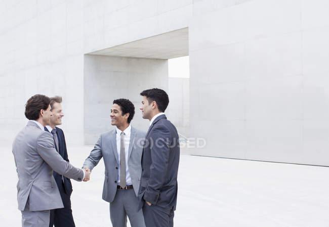 Усміхаючись бізнесменів, потискує руку за межами культурний центр — стокове фото