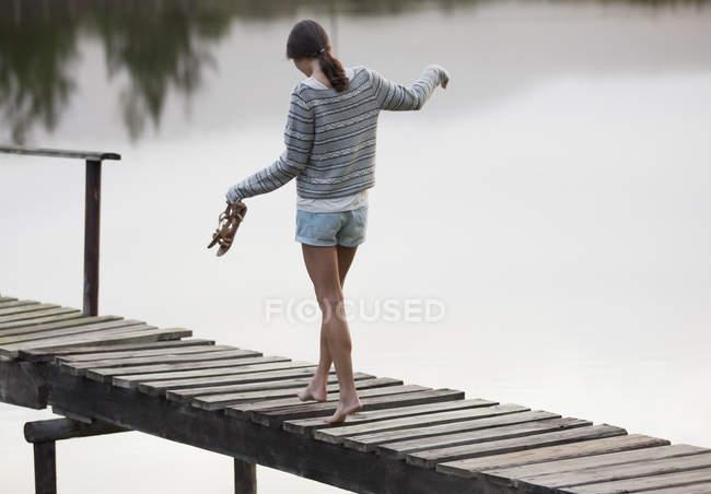 Donna che cammina lungo il molo sul lago — Foto stock