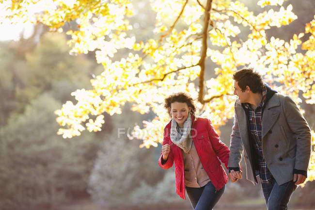 Feliz pareja caminando juntos en parque - foto de stock