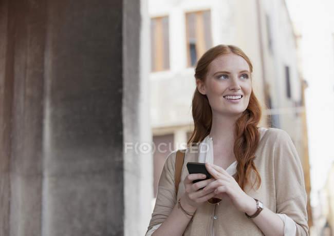 Sorrindo mulher segurando telefone celular — Fotografia de Stock