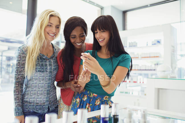 Women examining skincare products in drugstore — Stock Photo