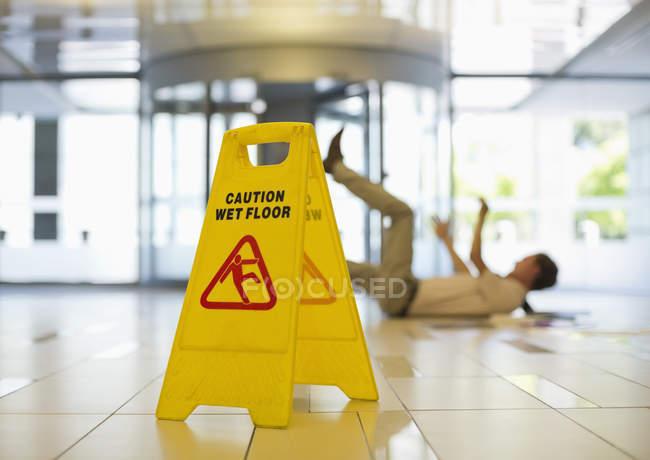 Businessman slipping on wet office floor — Stock Photo