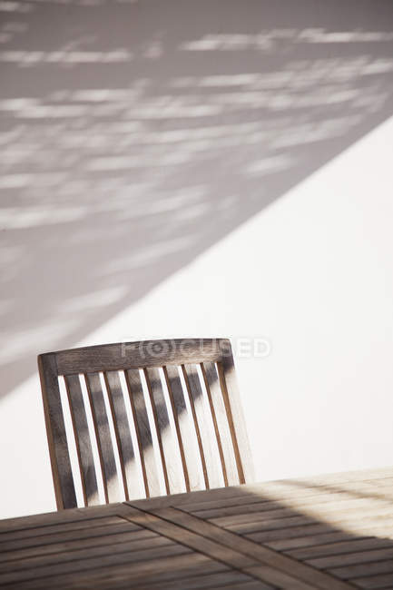 Mesa y silla de madera a la luz del sol - foto de stock