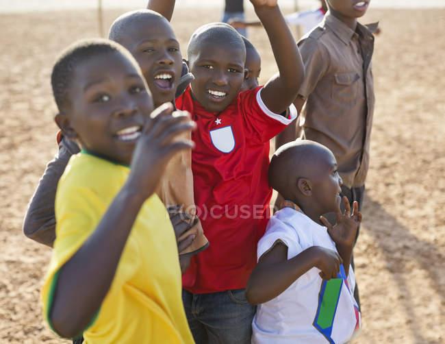 Африканские мальчики играют вместе на грязном поле — стоковое фото