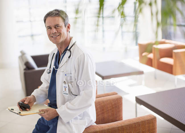 Portrait of smiling doctor in hospital lobby — Stock Photo