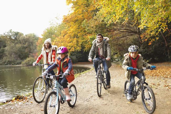 Счастливая семья верхом на велосипедах вместе в парке — стоковое фото