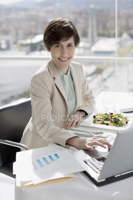 Portrait of smiling businesswoman eating lunch and working at desk — Stock Photo
