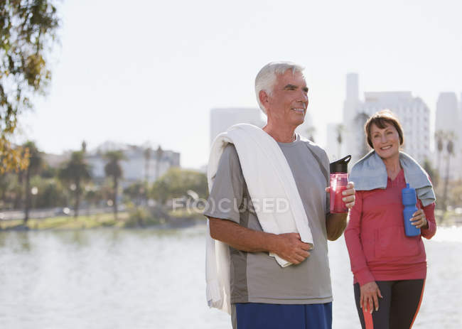 Older couple drinking water after workout — Stock Photo